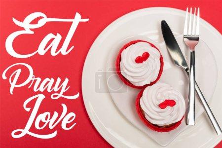Photo pour Vue du dessus de cupcakes sur assiette avec couverts près manger prier amour lettrage sur fond rouge - image libre de droit