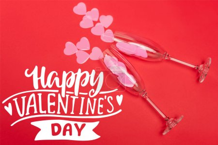 top view of paper hearts in champagne glasses near happy valentines day lettering on red background