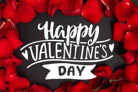 vue du dessus de joyeux lettrage Saint-Valentin dans le cadre avec des pétales de rose rouge sur noir