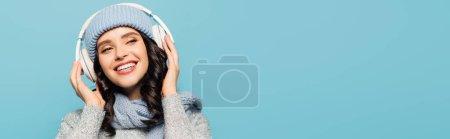 Photo pour Femme heureuse en chapeau et écharpe écoutant de la musique dans les écouteurs tout en regardant loin isolé sur bleu, bannière - image libre de droit