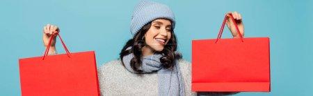 Positive brünette Frau mit Hut und Schal blickt auf rote Einkaufstasche vereinzelt auf blaues Banner