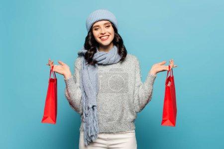 Photo pour Vue de face de la femme souriante en tenue d'hiver regardant la caméra tout en tenant des sacs à provisions rouges isolés sur bleu - image libre de droit