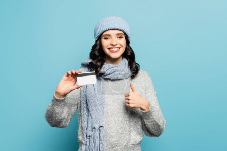 Photo for Happy brunette woman in winter outfit with credit card showing thumb up while looking at camera isolated on blue - Royalty Free Image