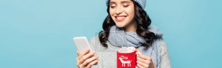 Cheerful brunette woman in scarf looking at smartphone while holding cup with knitted holder isolated on blue, banner