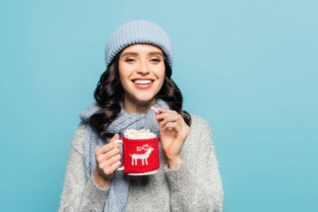 Front view of happy woman in hat and scarf holding cup and marshmallow while looking at camera isolated on blue