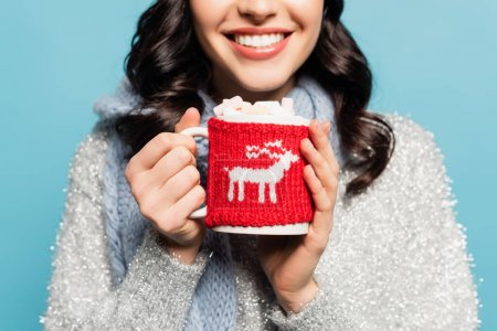 Cropped view of brunette woman in scarf holding cup with marshmallows and knitted holder isolated on blue