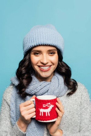 Happy brunette woman in hat and scarf looking at camera while holding cap with knitted holder isolated on blue