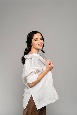 Photo pour Femme brune joyeuse regardant la caméra tout en enlevant la chemise blanche isolée sur gris - image libre de droit