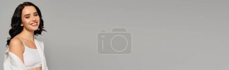 Photo for Happy brunette woman in white shirt and top looking at camera isolated on grey, banner - Royalty Free Image