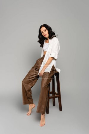 Full length of curly brunette woman in shirt and leather pants posing while sitting on stool on grey background