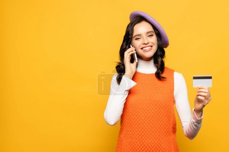 Smiling brunette woman in beret talking on smartphone and looking at camera while showing credit card isolated on yellow