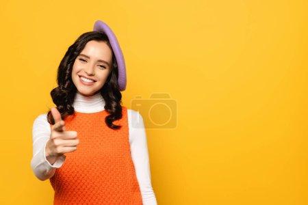 Foto de Mujer morena sonriente en boina apuntando con el dedo mientras mira a la cámara aislada en amarillo en primer plano borroso - Imagen libre de derechos