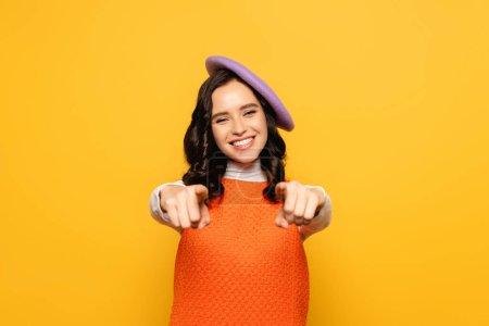 Positive brünette Frau mit Baskenmütze, die mit den Fingern zeigt, während sie die Kamera isoliert auf gelbem, unscharfem Vordergrund betrachtet