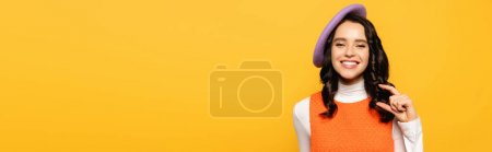 Positive brunette woman in beret showing small amount gesture while looking at camera isolated on yellow, banner