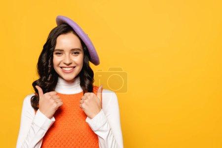 Photo pour Joyeux brunette femme en béret montrant pouces vers le haut tout en regardant la caméra isolée sur jaune - image libre de droit