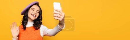 Glückliche Frau mit winkender Hand, Baskenmütze und Selfie auf gelbem Banner