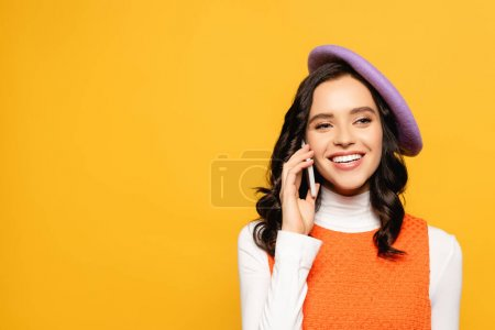 Cheerful brunette woman in beret looking away while talking on smartphone isolated on yellow
