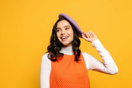 Cheerful brunette woman laughing and looking away while touching beret isolated on yellow