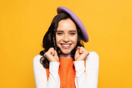 Happy brunette woman with yes gesture wearing beret and looking at camera isolated on yellow
