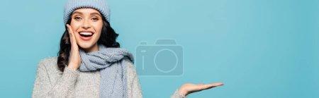 Photo pour Heureuse femme brune à bouche ouverte portant une tenue d'hiver et pointant avec la main isolée sur bleu, bannière - image libre de droit