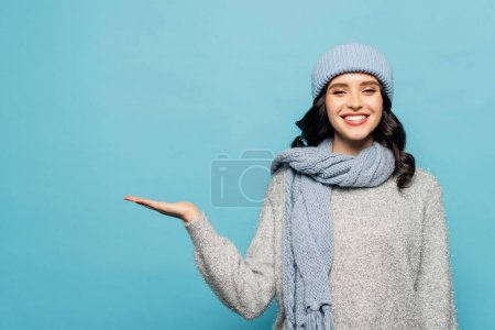 Photo for Front view of happy woman in winter outfit pointing with hand while looking at camera isolated on blue - Royalty Free Image