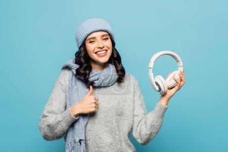 Photo pour Heureuse femme brune en tenue d'hiver tenant des écouteurs et montrant pouce vers le haut isolé sur bleu - image libre de droit