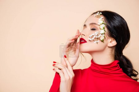 Photo for Young woman with red lips and flowers on face with closed eyes isolated on pink - Royalty Free Image