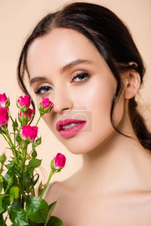 Photo for Young woman looking at camera near flowers isolated on pink - Royalty Free Image
