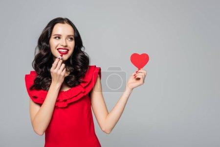 Photo pour Joyeuse jeune femme tenant coeur en papier rouge et rouge à lèvres isolé sur gris - image libre de droit