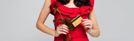 Photo for Cropped view of woman holding red rose and credit card isolated on grey, banner - Royalty Free Image