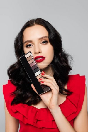 young brunette woman holding eye shadow palette isolated on grey