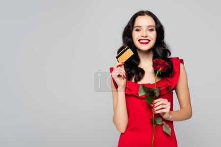 glückliche Frau mit roter Rose und Kreditkarte isoliert auf grau