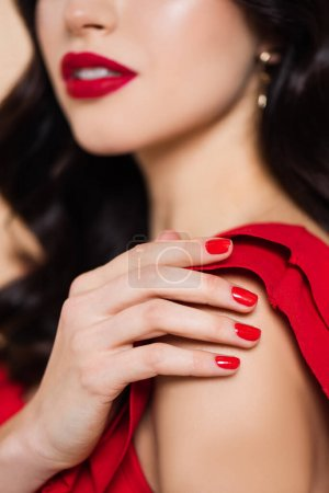 cropped view of brunette young woman with red lips touching shoulder isolated on pink