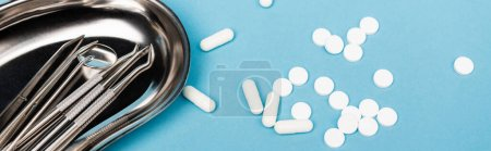 Photo for High angle view of dental tools on tray and pills on blue background, banner - Royalty Free Image