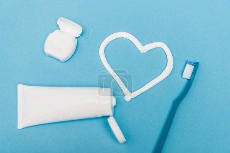 Photo pour Vue du dessus du fil dentaire, de la brosse à dents et du signe cardiaque du dentifrice sur fond bleu - image libre de droit