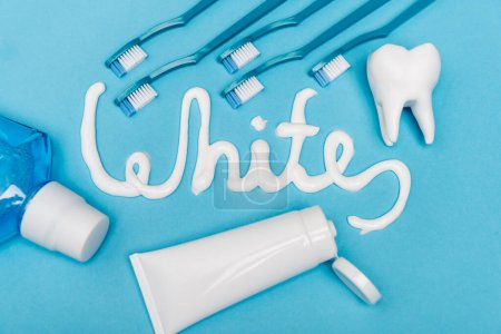Top view of white lettering from toothpaste, mouthwash and toothbrushes on blue background