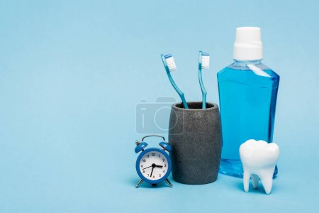 Small clock near toothbrushes, mouthwash and tooth model on blue background