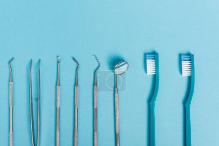 Photo for Top view of stainless dental tools and toothbrushes on blue background - Royalty Free Image