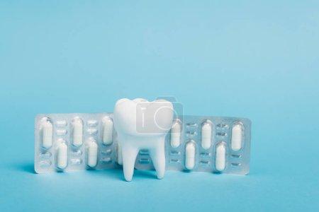 Zahnmodell in der Nähe von Blister mit Pillen auf blauem Hintergrund