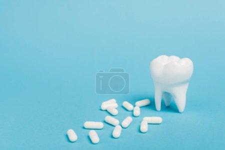Nahaufnahme weißer Pillen und Zahnmodell auf blauem Hintergrund