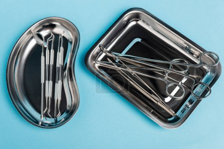 Photo for Top view of dental tools in stainless trays on blue background - Royalty Free Image