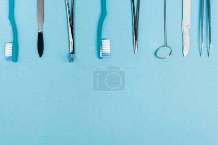 Draufsicht auf Reihe von Zahnwerkzeugen und Zahnbürsten auf blauem Hintergrund mit Kopierraum