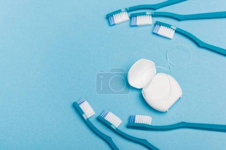 Photo pour Vue du dessus de la soie dentaire et des brosses à dents sur fond bleu - image libre de droit