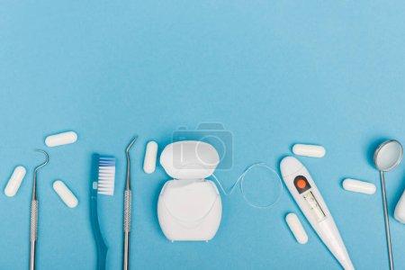 Photo pour Vue du dessus des outils dentaires, des pilules et du thermomètre sur fond bleu - image libre de droit