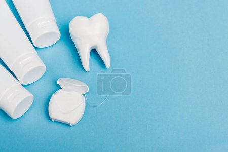 Photo for Top view of dental floss near tooth model and tubes with toothpaste on blue background - Royalty Free Image