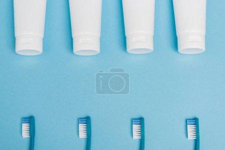 Photo pour Vue du dessus des tubes avec dentifrice et brosses à dents sur fond bleu - image libre de droit