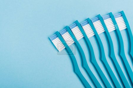 Photo for Top view of clean toothbrushes on blue background - Royalty Free Image