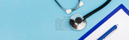 Photo pour Vue du dessus du presse-papiers et du stéthoscope sur fond bleu, bannière - image libre de droit