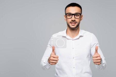 Photo pour Succès hispanique homme d'affaires souriant à la caméra et montrant pouces isolés sur gris - image libre de droit
