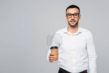 brunette hispanic manager with coffee to go smiling at camera isolated on grey
